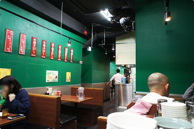 緑の壁が特徴的な店内。4~5名用のテーブル席が5つにカウンターが10席ほど。